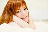 redhead young woman laying in bed