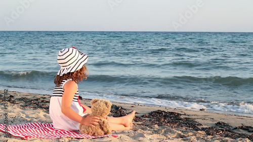 little girl with teddy bear sitting on beach