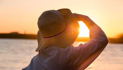 Young and beautiful woman wearing a hat in sunset light looking