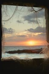 Finestra con rete di pescatori al tramonto