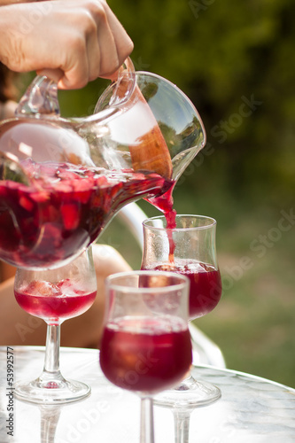 Hand serving sangria in a glass