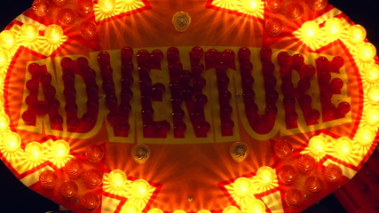 """adventure"" sign lit up by light bulbs at night"