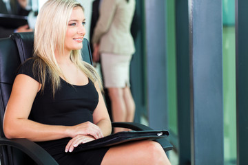 young blond businesswoman sitting in boardroom