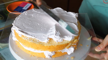 Baker decorating top layer with whipped cream