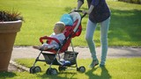 HD1080p25 Young woman pushes stroller with baby in the garden