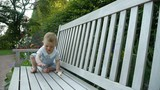 HD1080p25 Cute little baby playing with pacifier on a bench