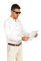 Amazed executive with sunglasses looking paper