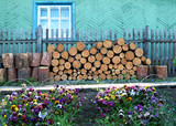 woodpile near a wooden fence and pansies poster