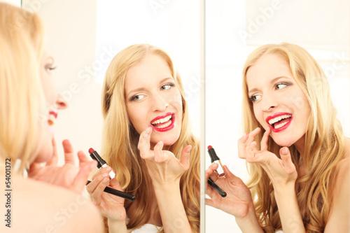 junge Frau trägt Lippenstift auf