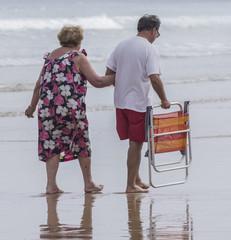 Anciana con hijo paseando por la orilla del mar