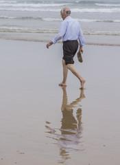 Anciano paseando por la orilla del mar