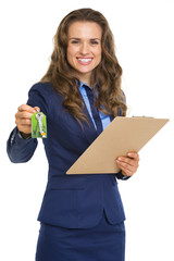 Smiling realtor woman giving with clipboard keys