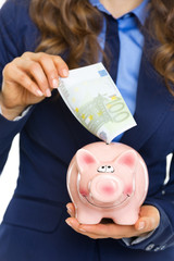 Business woman putting 100 euro banknote into piggy bank
