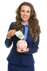 Smiling business woman putting 100 euro banknote into piggy bank