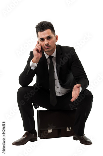 Businessman Talking on the phone while sitting on a briefcase