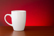 White mug on dark wooden table with red motled glow background