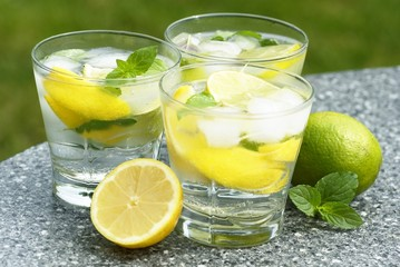 Fresh summer drink with ice cubes, lemon, lime and mint.