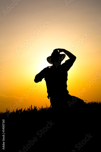 farmer in a field of wheat in the sunset