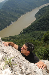 young man climbing up the rock