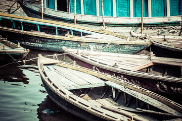 Old boats on brown waters of Ganges river, Varanasi, India