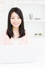 attractive asian woman using laptop in the room