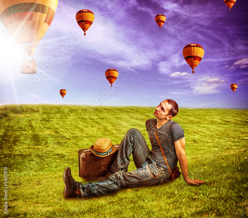 Young man traveler and flying aerostats