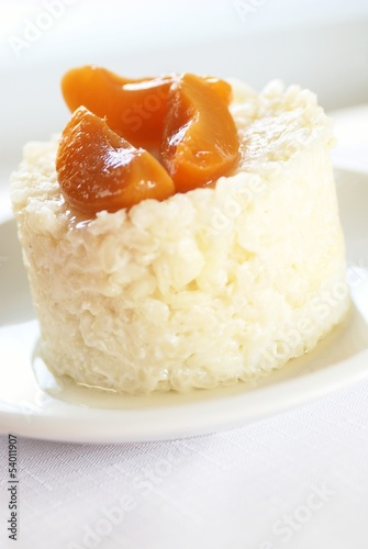 Sweet rice pudding with apricots on white plate.