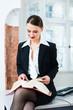 Anwältin in Kanzlei liest im Gesetzbuch