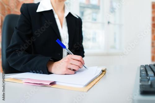 Anwältin in Kanzlei sitzt am Computer