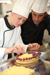 Pastry cook teaching student to make a cake