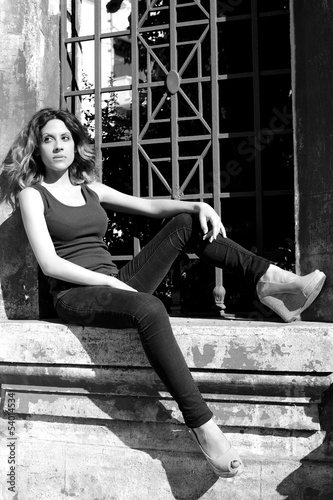 Portrait of woman serious sitting outdoors black and white