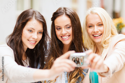 beautiful girls taking picture in cafe in city