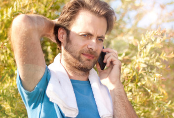 Businessman receiving a phone call during workout