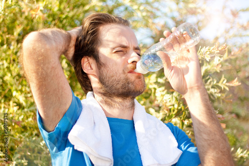 Forty years old man drinking water after workout
