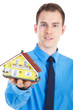 Junger Geschäftsmann überreicht miniatur Haus