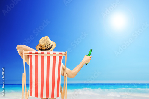 Man with hat sitting on a beach chair and holding a beer