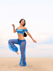 Full length portrait of a dancing girl in belly dance costume