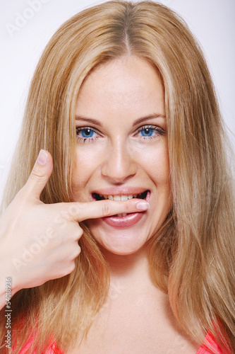 Happy blonde woman biting his finger. Isolated on white.