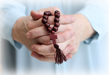 Image of parishioner's hands with wooden rosary