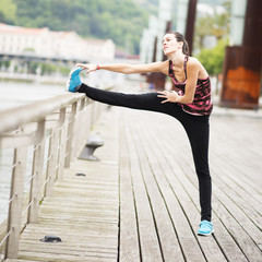 Young Woman Doing Stretches in the city.