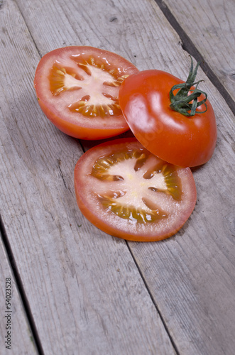 Organic sliced tomatoes on wooden background