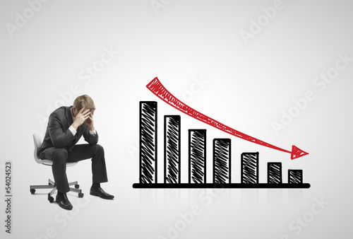 sad businessman sitting on chair with falling  chart