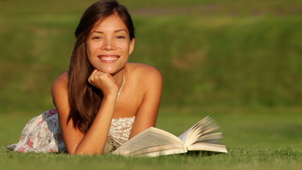 Girl reading book in park smiling happy