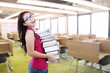 Beautiful student bring stack of books indoor