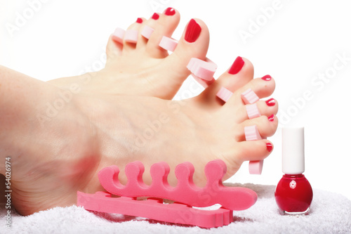 foot pedicure applying red toenails on white