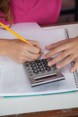Teenage Schoolgirl Using Calculator While Writing At Desk