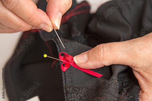 Woman sewing ribbon and rose to lingerie or bra