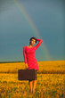 beautiful young woman in a pink dress holding retro suitcase