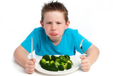 Grumpy young boy not happy about eating broccoli.