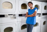 Female Helper Leaning On Dryers In Laundry